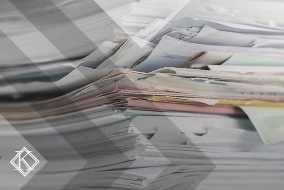 """A imagem mostra uma pilha de documentos, ilustrando a publicação """"Como conseguir provas de tempo especial para aposentadoria?"""", da Koetz Advocacia."""