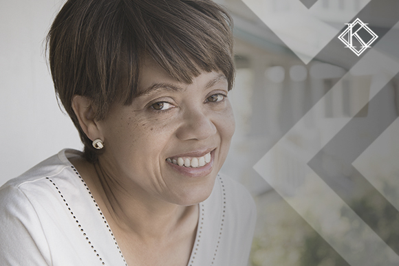 """Retrato de mulher sorrindo em frente à janela. A imagem ilustra a publicação """"Como contar tempo para aposentadoria no magistério?"""", da Koetz Advocacia."""
