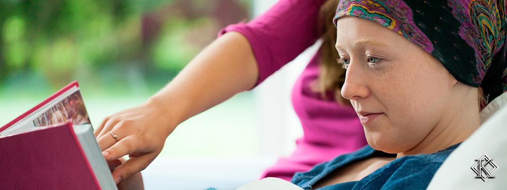 Paciente com câncer deitada em uma cama lendo um livro acompanhada de outra pessoa. Imagem ilustra a possibilidade de aposentadoria por invalidez ou de auxílio doença para pessoas com a doença.
