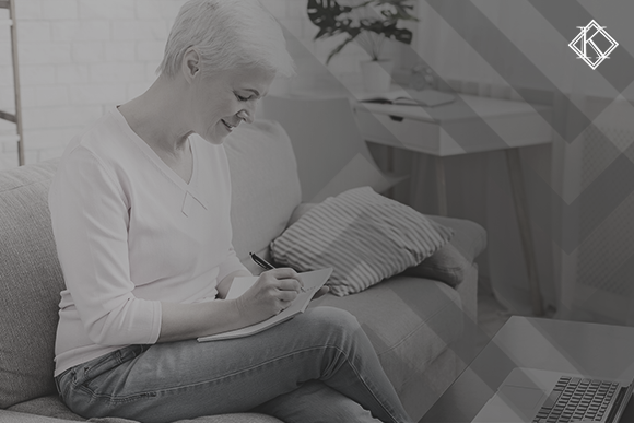 """Imagem de uma senhora de cabelos grisalhos sentada no sofá da sala de cabeça abaixo com um papel e uma canetada na mão . A imagem tem um filtro cinza de acordo com a identidade visual da Koetz Advocacia. No canto superior direito está a logo branca da Koetz Advocacia. A imagem ilustra o texto """"Critérios para garantir a paridade e integralidade na aposentadoria """"."""