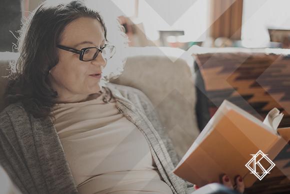 A imagem mostra uma mulher lendo um livro ou apostila no sofá, e ilustra a publicação