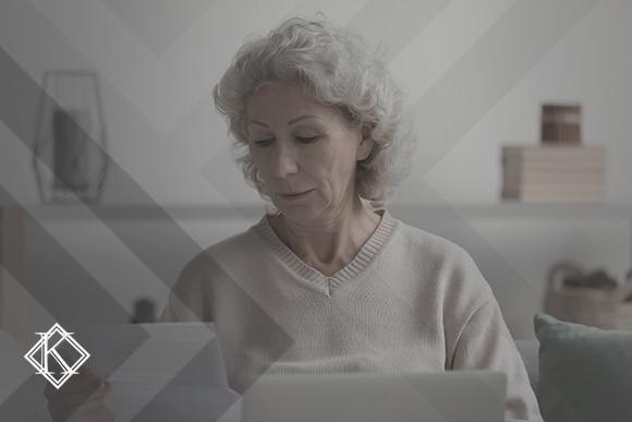 """A imagem mostra uma mulher lendo documentos e ilustra a publicação """"Quanto tempo demora um processo previdenciário?"""", da Koetz Advocacia."""