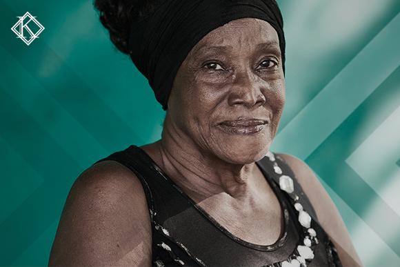 """A imagem mostra uma mulher à frente de um quadro verde desfocado. Ela ilustra a publicação """"Complementação da aposentadoria de professor pelo Direito Adquirido"""", da Koetz advocacia."""