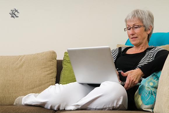 A imagem mostra uma mulher de idade descansando em seu sofá com um notebook. Veja aqui 5 casos comuns de doenças ocupacionais do enfermeiro.