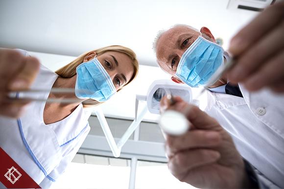 A imagem mostra dois dentistas trabalhando com seus aparelhos. Saiba mais sobre a aposentadoria por invalidez do dentista.