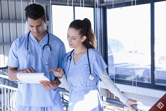 A imagem mostra um enfermeiro e uma enfermeira trabalhando em conjunto em seu ambiente de trabalho. Saiba mais sobre os direitos previdenciários na enfermagem aqui.