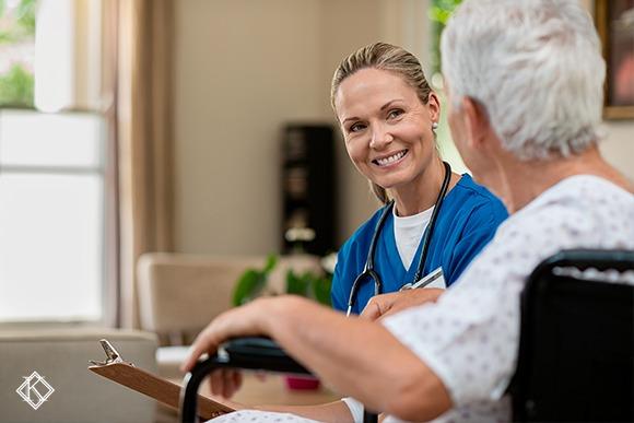Enfermeira com cabelo preso, roupa azul, falando com um paciente de cerca de 60 anos vestido de branco
