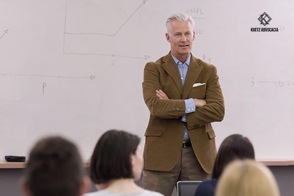 A imagem mostra um professor dando sua aula em uma sala.