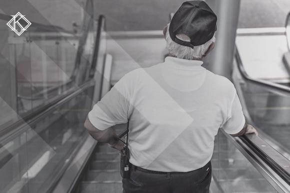 Segurança descendo escada rolante, fotografado de costas. A imagem ilustra a publicação