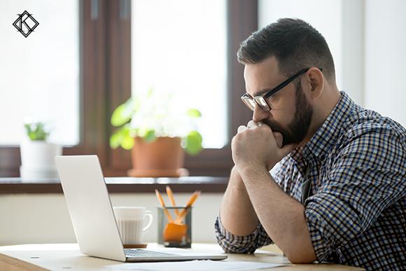 Homem olhando a tela do computador preocupado