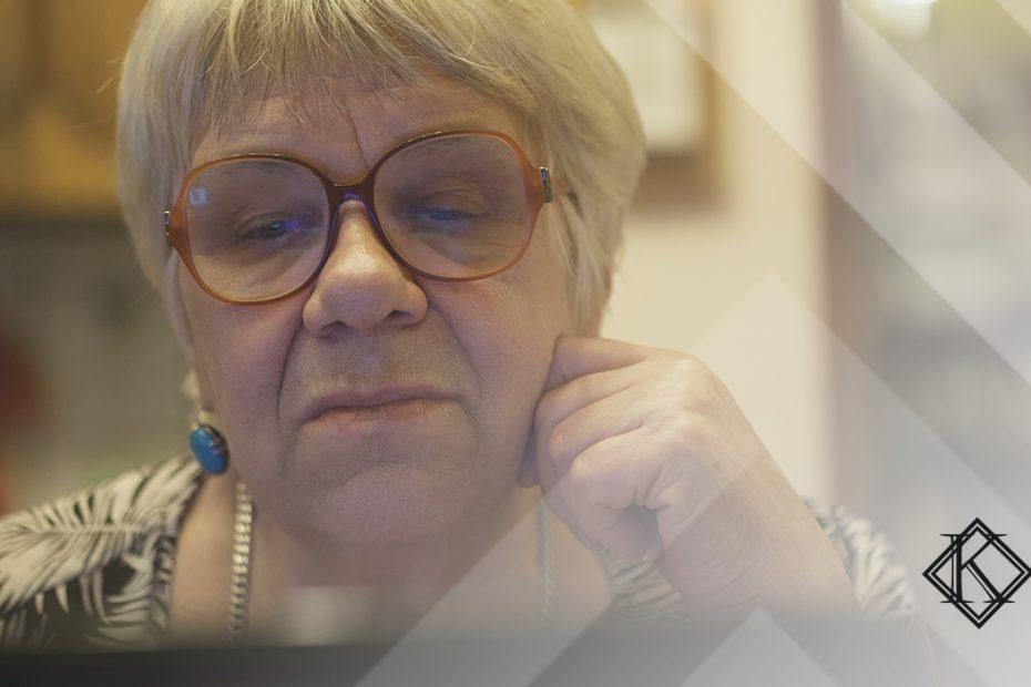 """A imagem mostra uma mulher concentrada olhando para o computador, e ilustra a publicação """"Indeferido no INSS: o que significa e o que fazer nesse caso?"""", da Koetz Advocacia."""