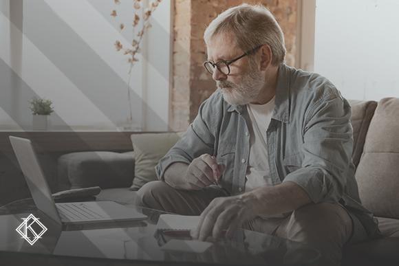 """Imagem de um senhor de cabelos e barba grisalha, usando óculos de grau, sentado no sofá da sala segurando uma caneta e olhando para seu notebook em cima da mesa, aonde também se encontra um caderno. A imagem tem um filtro cinza de acordo com a identidade visual da Koetz Advocacia. No canto inferior esquerdo está a logo branca da Koetz Advocacia. A imagem ilustra o texto """"Aposentadoria Especial é uma recompensa e permite seguir trabalhando""""."""