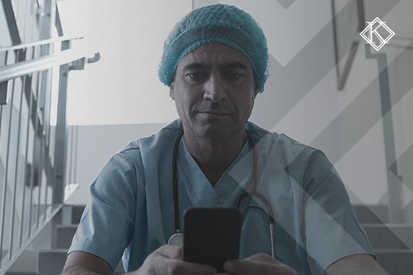 Enfermeiro sentado em escada olhando para o celular. A imagem ilustra a publicação