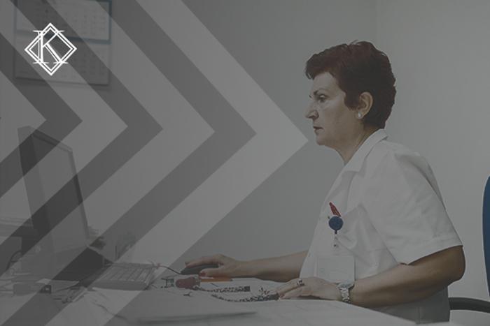 """Imagem de uma senhora usando jaleco sentada na frente do computador, em cima da mesa encontra-se papéis, carimbo e canetas. A imagem tem um filtro cinza de acordo com a identidade visual da Koetz Advocacia. No canto superior esquerdo está a logo branca da Koetz Advocacia. A imagem ilustra o texto """"Aposentadoria Especial para Funcionários de Hospitais e Postos de Saúde."""""""