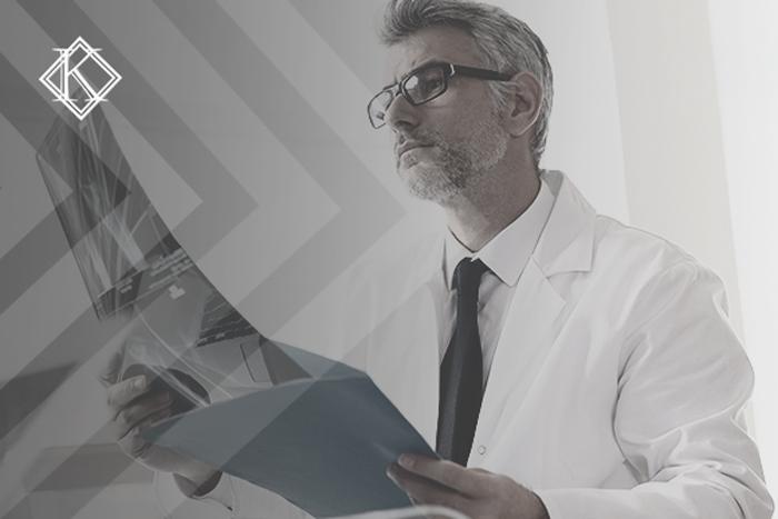 """Imagem de um homem de cabelos e barba grisalhos usando óculos de grau, olhando raio x de um paciente. A imagem tem um filtro cinza de acordo com a identidade visual da Koetz Advocacia. No canto superior esquerdo está a logo branca da Koetz Advocacia. A imagem ilustra o texto """"Aposentadoria dos Radiologistas com Tempo Especial."""""""