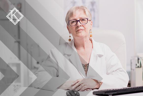 Médica sentada na mesa de consultório. A imagem ilustra a publicação