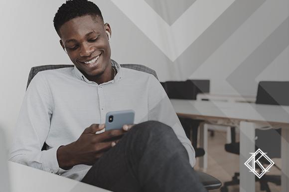 """A imagem mostra um homem sorrindo e lendo algo no celular. Ilustra a publicação """"Contrato de Trabalho no Exterior: o que devo saber?"""", da Koetz Advocacia."""