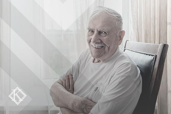 """A imagem mostra um homem de idade avançada sorrindo, sentado em uma cadeira. A imagem ilustra a publicação """"Reintegração de Servidor Público Municipal aposentado pelo INSS após a reforma"""", da Koetz Advocacia."""