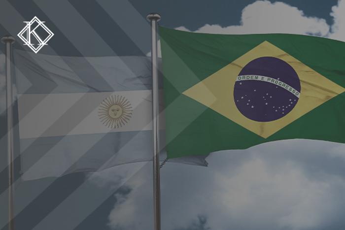 """Imagem da bandeira da Argentina e da bandeira do Brasil, no fundo um céu azul. A imagem tem um filtro cinza de acordo com a identidade visual da Koetz Advocacia. No canto superior esquerdo está a logo branca da Koetz Advocacia. A imagem ilustra o texto """"Acordos de Previdência da Argentina com o Brasil: como se aplicam?"""""""