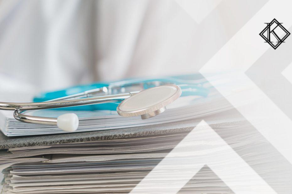 """A imagem mostra uma pilha de documentos com um estetoscópio em cima, e ilustra a publicação """"Como agendar pericia médica para funcionário"""", da Koetz Advocacia."""