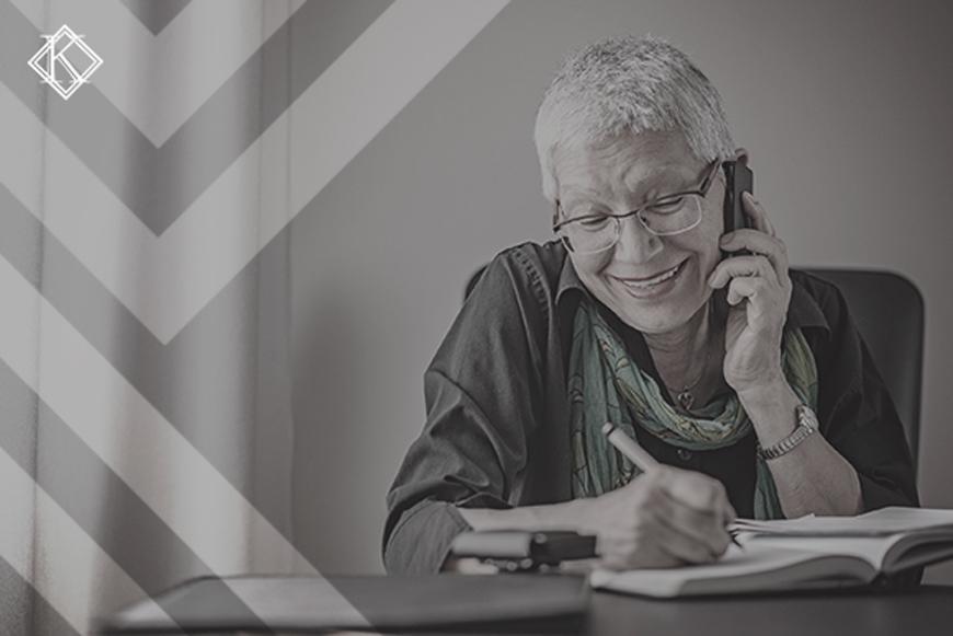 """Imagem de uma senhora usando óculos de grau, sentada em uma mesa, segurando o celular no ouvido, na outra mão escrevia com uma caneta no caderno que está em cima da mesa. A imagem tem um filtro cinza de acordo com a identidade visual da Koetz Advocacia. No canto inferior superior está a logo branca da Koetz Advocacia. A imagem ilustra o texto """" Complementação de aposentadoria para servidor municipal antes e depois da reforma""""."""