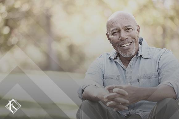 """A imagem mostra um homem sentado em um banco em uma praça sorrindo para a câmera. A foto ilustra a publicação """"Garantir seus direitos previdenciários em 5 passos importantes""""."""