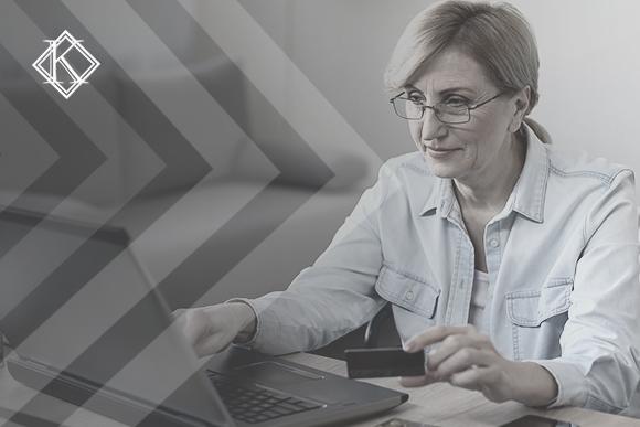 """Mulher de aproximadamente 50 anos de idade de óculos de grau e camisa em frente ao notebook. Sobre a imagem há grafismos da identidade visual e o logo da Koetz Advocacia. A imagem ilustra o texto """"Aposentadoria integral em municípios sem regime próprio de previdência."""""""
