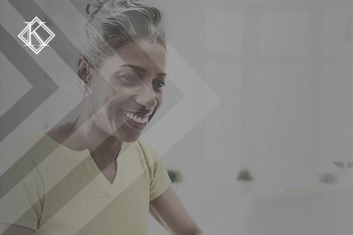 """Imagem de uma senhora sorrindo sentada na frente do notebook. A imagem tem um filtro cinza de acordo com a identidade visual da Koetz Advocacia. No canto superior esquerdo está a logo branca da Koetz Advocacia. A imagem ilustra o texto """"Servidor aposentado pode ter reintegração no cargo? Entenda?"""""""