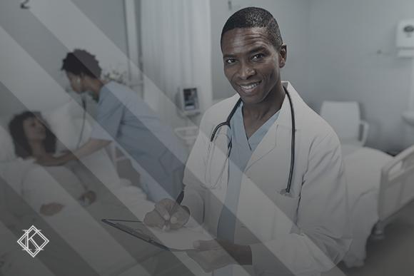 """Imagem composta por um médico negro, com estetoscópio no pescoço, segurando uma prancheta e uma caneta, no fundo uma enfermeira de pele negra examinando uma paciente de pele branca. A imagem tem um filtro cinza de acordo com a identidade visual da Koetz Advocacia. No canto inferior esquerdo está a logo branca da Koetz advocacia. A imagem ilustra o texto """"Aposentadoria de Médicos Cubanos no Brasil: quais as opções?."""""""