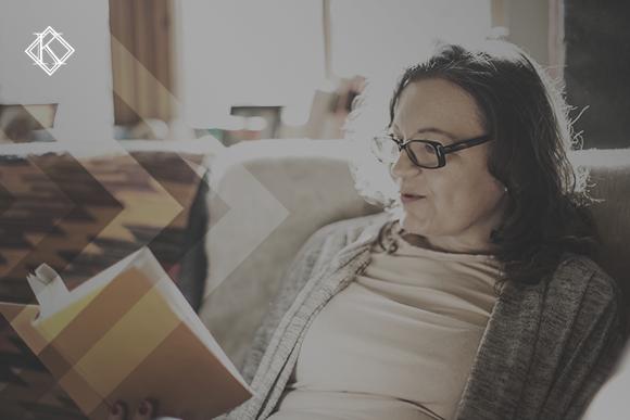 """Imagem de uma senhora sentada na sua sala de estar usando óculos lendo um livro. A imagem tem um filtro marrom com cinza de acordo com a identidade visual da Koetz Advocacia. No canto superior esquerdo está a logo branca da Koetz Advocacia. A imagem ilustra o texto """" Integralidade na Aposentadoria de Servidor: condição para gerar vacância"""""""