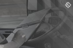 """Imagem de uma mão com uma caneta preenchendo um caderno em cima do volante do caminhão . A imagem tem um filtro cinza de acordo com a identidade visual da Koetz Advocacia. No canto superior direito está a logo branca da Koetz Advocacia. A imagem ilustra o texto """"Aposentadoria de Caminhoneiro com Tempo Especial """"."""