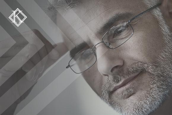"""Imagem de um homem de cabelos e barba grisalhos usando óculos de grau, com a mão na cabeça, com a expressão de pensando.A imagem tem um filtro cinza de acordo com a identidade visual da Koetz Advocacia. No canto superior esquerdo está a logo branca da Koetz Advocacia. A imagem ilustra o texto """"Servidor do INSS tem direito à Aposentadoria Especial ."""""""