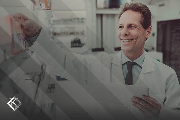 Imagem de um homem vestido com jaleco branco segurando uma prancheta e repondo um produto na prateleira de uma farmácia. A imagem tem um filtro cinza de acordo com a identidade visual da Koetz Advocacia. No canto inferior esquerdo está a logo branca da Koetz Advocacia. A imagem ilustra o texto