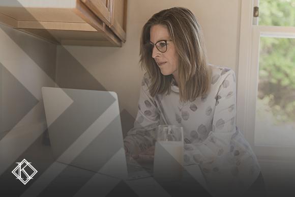 """Imagem de uma mulher usando óculos de grau em pé debruçada na mesa de frente para o notebook, ao lado um copo de leite . A imagem tem um filtro cinza de acordo com a identidade visual da Koetz Advocacia. No canto inferior esquerdo está a logo branca da Koetz Advocacia. A imagem ilustra o texto """"Como renegociar aluguel comercial na quarentena do coronavírus?""""."""