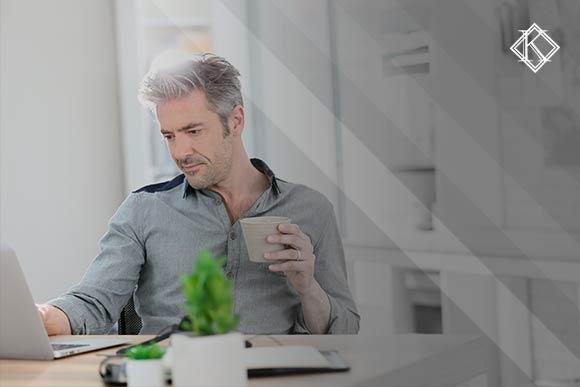 """Imagem de um homem de cabelos e barba grisalhas, sentado de frente para o notebook segurando um copo, na mesa se encontra dois vasos e uma prancheta. A imagem tem um filtro cinza de acordo com a identidade visual da Koetz Advocacia. No canto superior direito está a logo branca da Koetz Advocacia. A imagem ilustra o texto """"Decisões favoráveis à reintegração de servidor estátutário""""."""