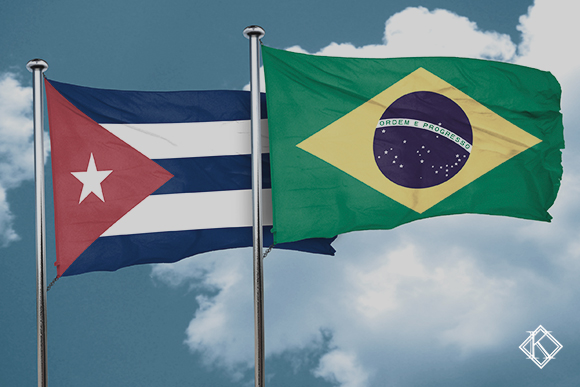 """Imagem da bandeira do Brasil e de Cuba, no fundo um céu azul com nuvens. A imagem tem um filtro cinza de acordo com a identidade visual da Koetz Advocacia. No canto inferior direito está a logo branca da Koetz Advocacia. A imagem ilustra o texto """"Acordo de Previdência Brasil e Cuba: quais os direitos e como funciona?""""."""