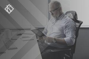 """Imagem de um senhor de barba e cabelos grisalhos, sentado na frente do computador segurando uma agenda, na mesa encontra-se também um caderno, caneta e uma xícara de café. A imagem tem um filtro cinza de acordo com a identidade visual da Koetz Advocacia. No canto superior esquerdo está a logo branca da Koetz Advocacia. A imagem ilustra o texto """"Aposentadoria de Empresário: como conquistar o melhor o benefício?""""."""