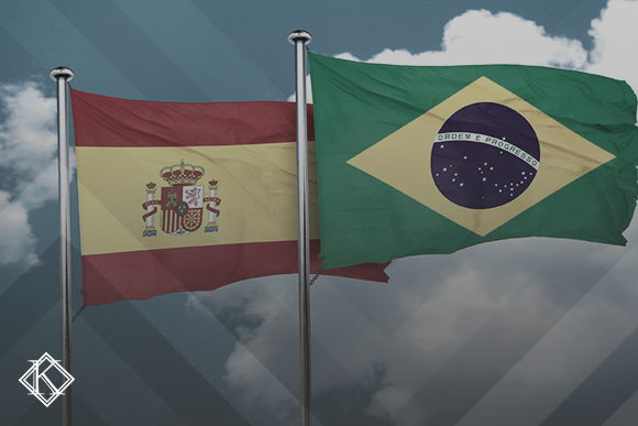 """Bandeiras do Brasil e da Espanha com o céu ao fundo. Imagem ilustrando a publicação """"Acordo Previdenciário entre Brasil e Espanha: quais os direitos?"""", da Koetz Advocacia."""