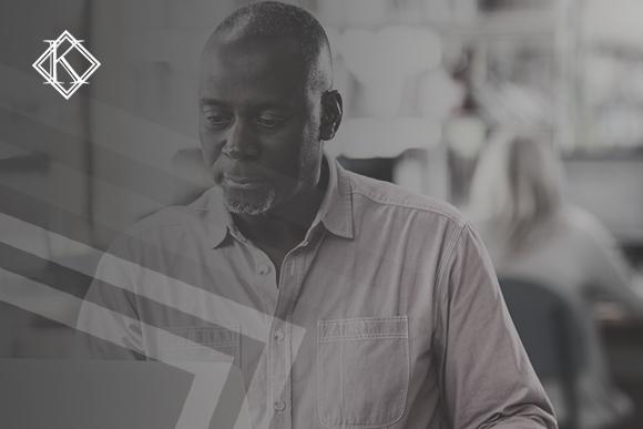 """Imagem de um homem sentado na frente do notebook. A imagem tem um filtro cinza de acordo com a identidade visual da Koetz Advocacia. No canto superior esquerdo está a logo branca da Koetz Advocacia. A imagem ilustra o texto """"Certidão de Tempo de contribuição: como obter e quais vantagens."""""""
