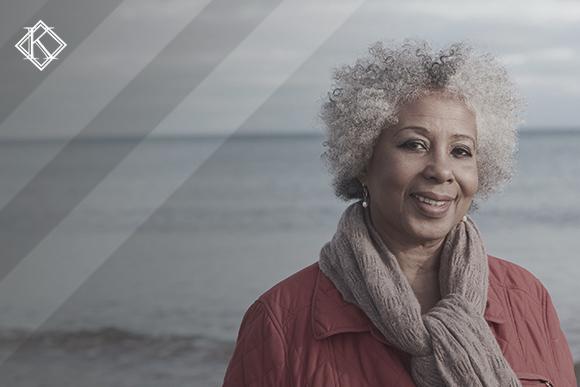 """Retrato de uma mulher na praia olhando para a câmera. A imagem ilustra a publicação """"Complementação de aposentadoria na Reforma da Previdência: Como ficou?"""""""