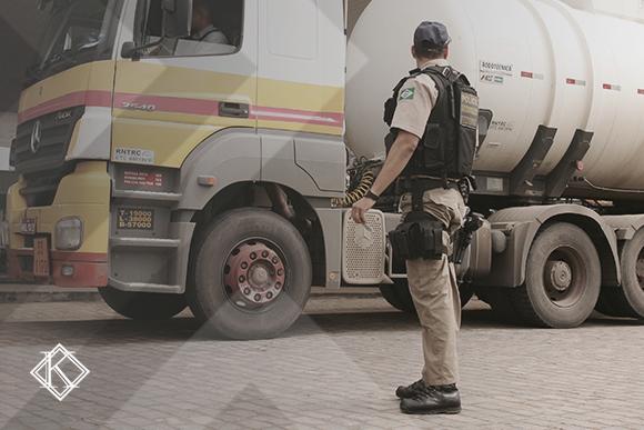 A imagem mostra um policial federal rodoviário em frente a um caminhão. A imagem ilustra a publicação