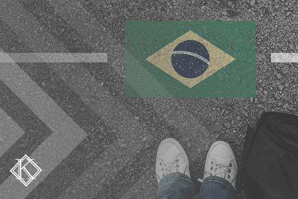 """Imagem de uma estrada aonde aparece os pés de um homem e uma mala ao lado, na sua frente a bandeira do Brasil pintada no asfalto. A imagem tem um filtro cinza de acordo com a identidade visual da Koetz Advocacia. No canto inferior direito está a logo branca da Koetz Advocacia. A imagem ilustra o texto """"Quando um imigrante tem direito de permanecer no Brasil?""""."""