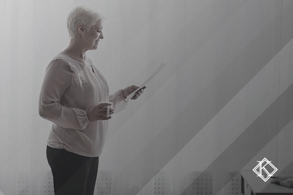 """Mulher lendo algo em uma folha de papel em sua mão. A imagem ilustra a publicação """"Regime Próprio Complementar na Aposentadoria do Servidor Municipal"""""""