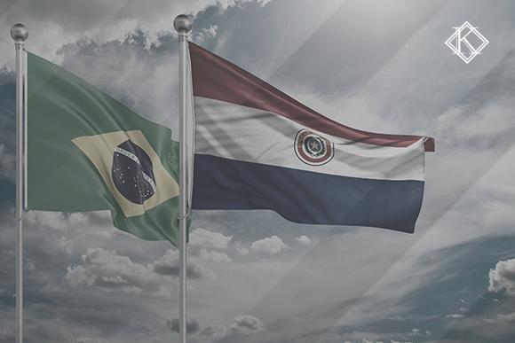 """Bandeiras do Brasil e do Paraguai. A imagem ilustra a publicação """"Acordo de Previdência entre Paraguai e Brasil: como beneficia segurados?"""", da Koetz Advocacia."""