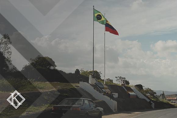 Rodovia com paisagem rural e bandeiras do Brasil e Venezuela. A imagem ilustra a publicação