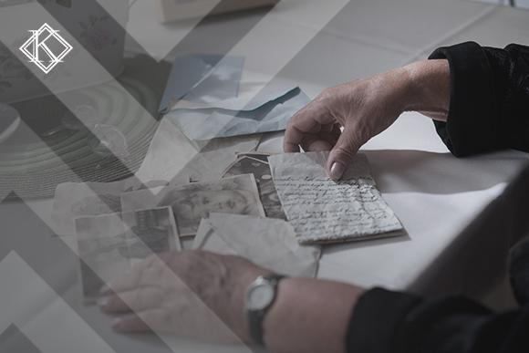 """Mãos manipulando documentos e fotos antigas. A imagem ilustra a publicação """"Pensão por Morte no RPPS da União: regras e direito ao benefício"""", da Koetz Advocacia."""