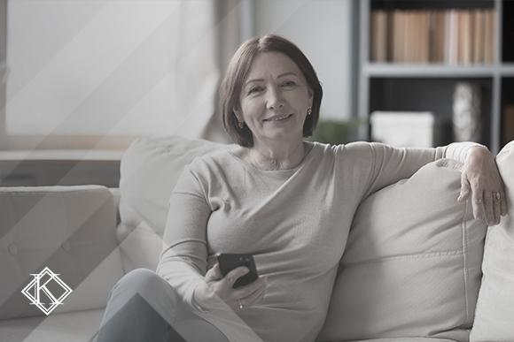 """Mulher sentada com o celular na mão, sorrindo para a câmera. A imagem ilustra a publicação """"Aposentadoria de Imigrante que trabalhou em dois países"""", da Koetz Advocacia."""