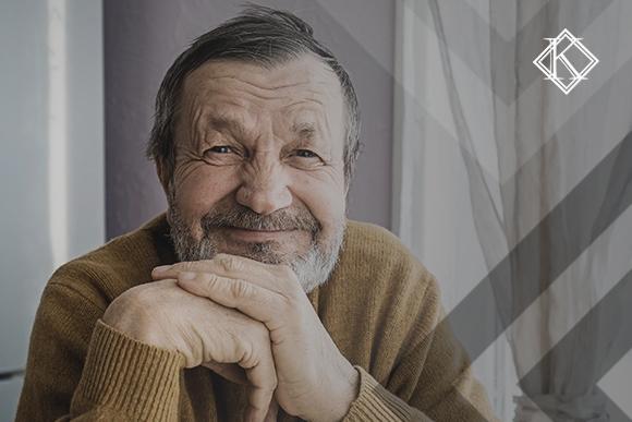 """Homem sorrindo para a câmera. A imagem ilustra a publicação """"Como fazer prova de vida no INSS estando no exterior?"""", da Koetz Advocacia."""