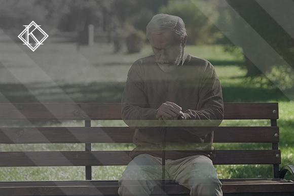 """A imagem mostra um homem sentado em um banco de uma praça """"desaparecendo"""", isto é, ficando transparente. Ilustra a publicação """"Duração da Pensão por Morte do Servidor Público Federal"""", da Koetz Advocacia."""