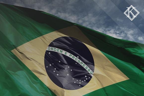 """Close da bandeira do Brasil com céu azul no fundo. A imagem ilustra a publicação """"Exportação de benefícios previdenciários e quebra de acordos pelo Brasil"""", da Koetz Advocacia."""
